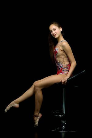 Girl gymnast sits on rotating chairs on a black background in th