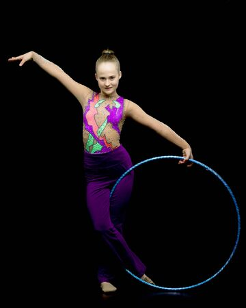 A girl gymnast performs an exercise with a hoop. Imagens