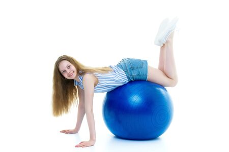 little girl is engaged in fitness with a ball.