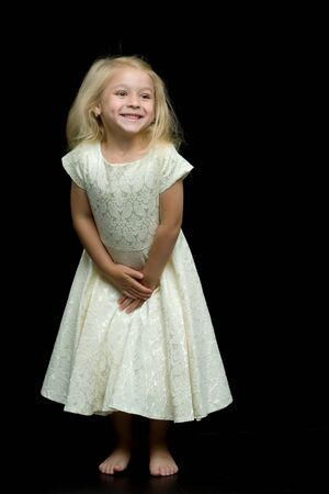 Portrait of a cute little girl on a black background. Happy chil