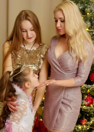 Mom with her daughters near the New Year tree.