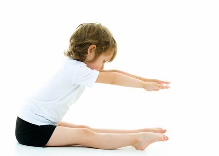 Charming little girl doing gymnastic exercises in the studio on