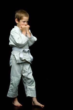 Ein kleiner Junge im weißen Kimono vollführt Schläge