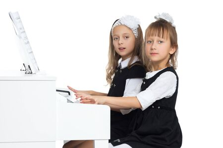 Girls play the piano. Isolated on white background