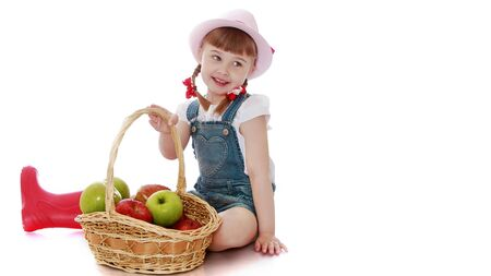 Little girl with a basket of apples.Isolated on white background Banque d'images