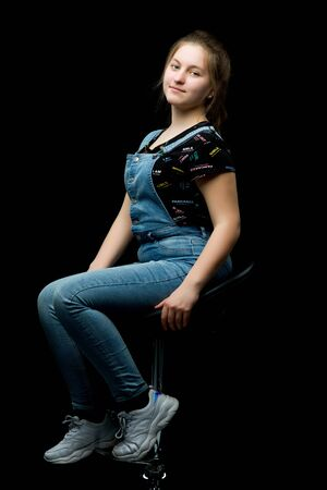 Charming girl teenager sitting on a chair in the studio on a bla
