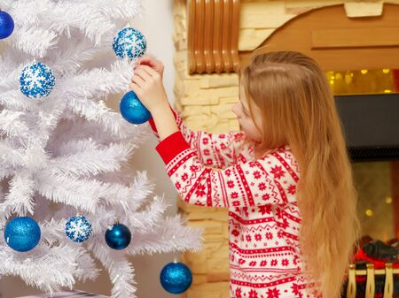 A happy little girl is decorating a Christmas tree. The concept of holidays, Christmas and New Year. Isolated on white background.