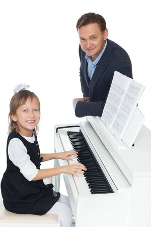 Teacher and student at piano. Isolated on white background