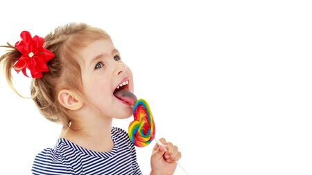 Girl licks candy on a stick. Isolated on a white background.