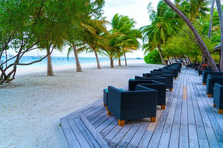 Wooden table and chairs by the tropical warm sea. Maldives Stok Fotoğraf
