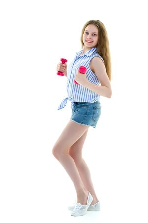 Teenage girl with dumbbells in hands