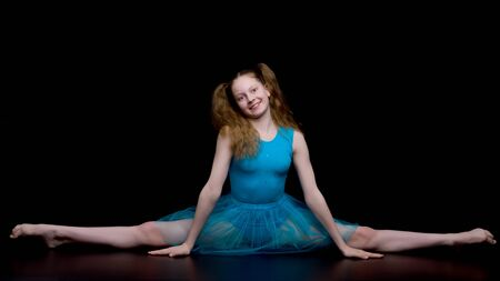 Girl gymnast in the studio on a black background performs gymnas 写真素材