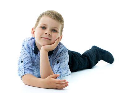 Happy little boy is lying on the floor in the studio.