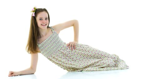 Teen girl lies in the studio on a white background.
