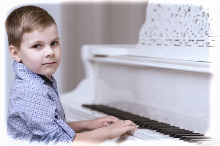 Little boy in studio near white piano.
