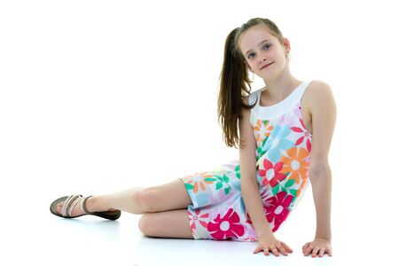 Teen girl posing on the floor in the studio. The concept of styl