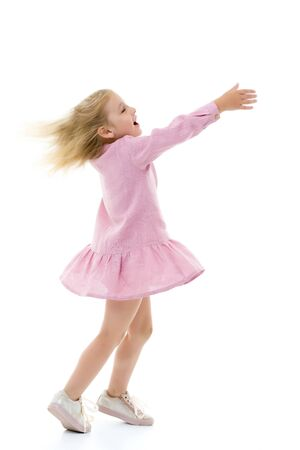 A little girl in a dress is spinning. Imagens