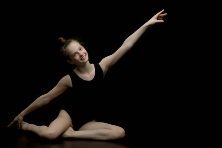Girl gymnast in the studio on a black background performs gymnas 스톡 콘텐츠