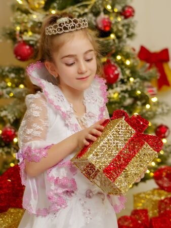 Little girl near the Christmas tree with a gift. Foto de archivo - 133517370
