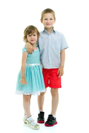 Boy and girl, brother and sister posing in the studio. Concept of family values, friendship, game. Isolated on white background Foto de archivo - 133517371
