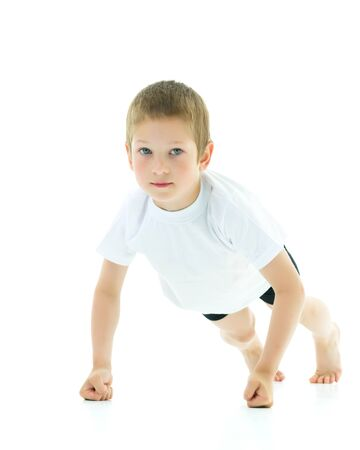 Cute little boy performs gymnastic exercises. Isolated on white background Sport concept, happy childhood