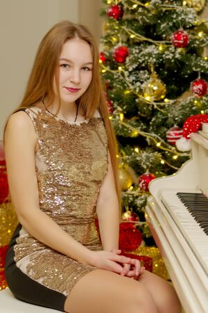 Teenage girl near the New Year tree behind the keys of a white p Foto de archivo - 133517376