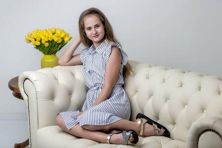 Beautiful little girl with long silky hair, sits on the couch with a bouquet of yellow tulips. The concept of happy people, style and fashion.