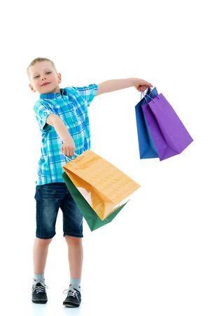 Little boy waving multicolored paper bags. He goes shopping Foto de archivo - 133517412
