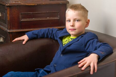 Cute little boy sitting on the armchair in the studio. The concept of family and people. Foto de archivo - 133517421
