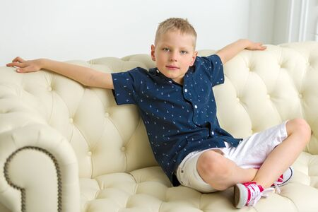 A little boy is sitting in the studio on a white sofa. The conce Foto de archivo - 133517492