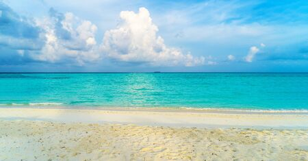 Only white sand, warm azure sea, thick cumulus clouds on the shore of a paradise island. Maldives, tourist paradise. Panorama.