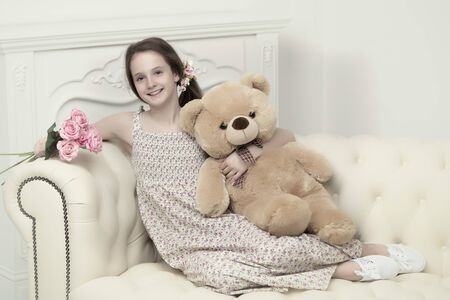 Beautiful teenager girl of school age sitting on the couch with Stock fotó
