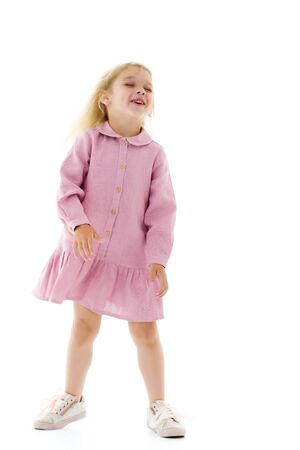 A little girl in a dress is spinning. 스톡 콘텐츠