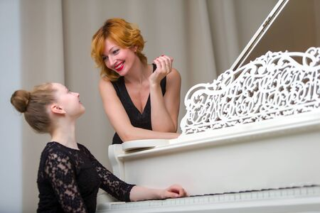 mother with her daughter together at the piano Stok Fotoğraf