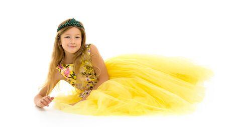 Little girl lies on the floor.Studio photo shoot on a white back Foto de archivo - 133517626