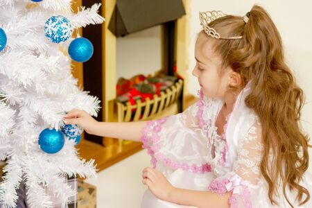A little girl is decorating a Christmas tree. Foto de archivo - 133517627