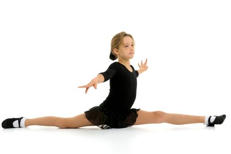 Slender girl gymnast doing the twine. The concept of childrens