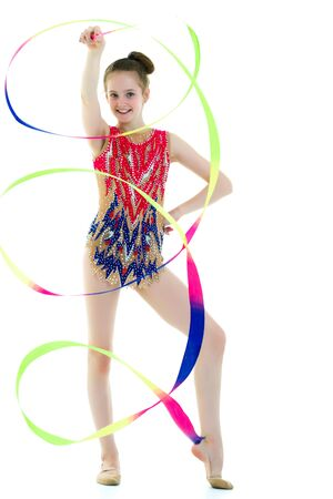 Girl gymnast performs exercises with tape. Banco de Imagens