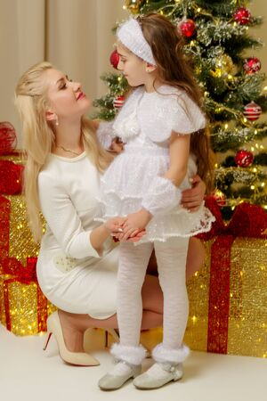 Mom with a little daughter at the Christmas tree. Foto de archivo - 133517648