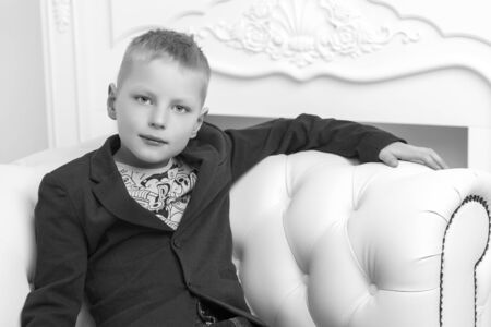 A little boy is sitting in the studio on a white sofa. The conce Foto de archivo - 133517654