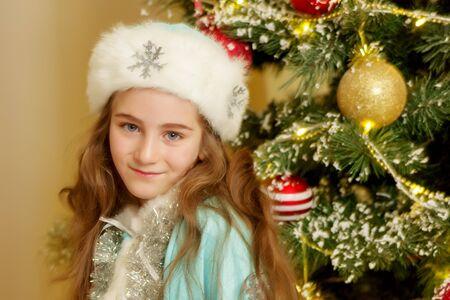 Little girl Snow Maiden near the New Year tree. Foto de archivo - 133517832