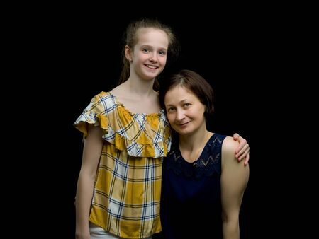 Mom and daughter in the studio on a black background. Foto de archivo - 133517836