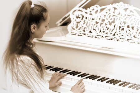 A teenage girl is playing on a white grand piano.