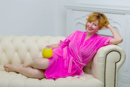 Beautiful young woman in a bathrobe relaxes on a sofa by the fir