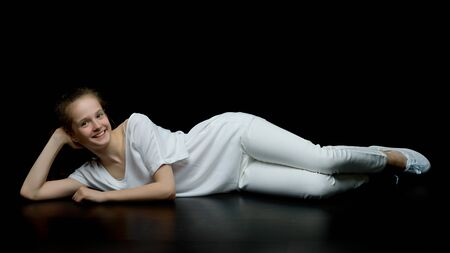 Cute little girl lying on the floor in the studio on a black bac Foto de archivo