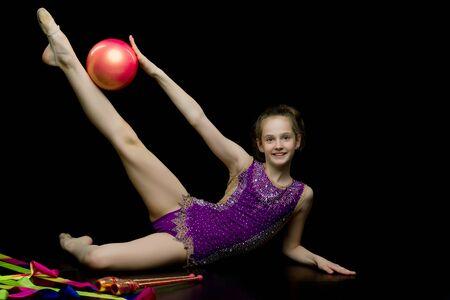 Meisje gymnast voert oefeningen met de bal.