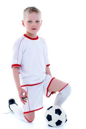 A little boy wearing a pure white t-shirt is playing with a soccer