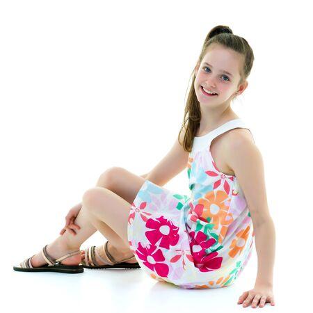 A teenage girl is sitting on the floor. Imagens