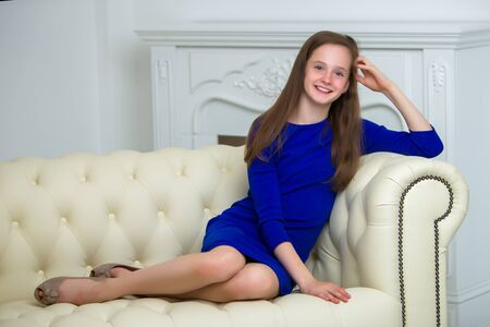 Beautiful young girl sitting on the sofa by the fireplace