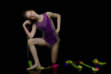 Meisje gymnast voert oefeningen met tape.